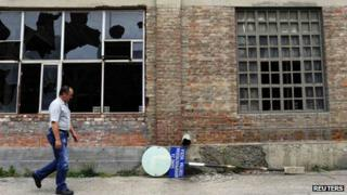 "A worker passes by an abandoned production hall at the ""Zastava Arms"" weapons factory in the Serbian town of Kragujevac"