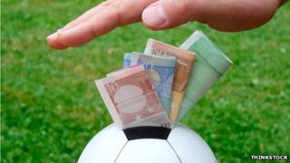Hand pushing money into a football