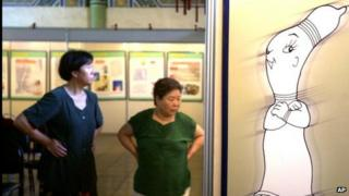 Chinese women walk next to a poster promoting condom use at a sex education exhibition in Beijing