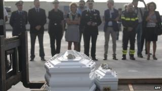Officials pay their respect in front of the coffins of refugees who died trying to get to Lampedusa