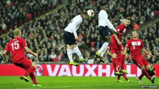 Wayne Rooney heading the ball against Poland