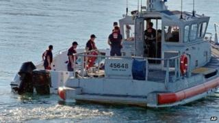 US Coast Guard personnel climb aboard the power boat to examine it