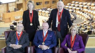 Five of the six winners of the Carnegie Medal of Philanthropy 2013 are pictured in the debating chamber of the Scottish Parliament (Back Row: Dame Janet Wolfson de Botton, Dr. James Simons; Front row: Dr Dmitry Zimin, Sir Tom Hunter and Dr Marilyn Simons)