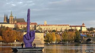 Workers anchor a boat bearing an installation work by Czech visual artist David Cerny in front of the Prague Castle