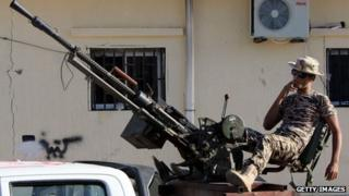 A Libyan 'citizen soldier' smokes a cigarette on the back of an armed vehicle in Benghazi in October 2012