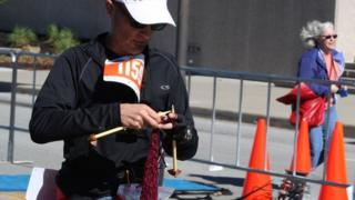David Babcock knitting just before he finished running the marathon