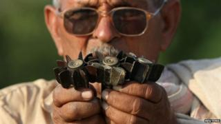 An Indian villager shows shells, that locals say are being fired from the Pakistan, at a village in Samba sector, about 75km (47 miles) from Jammu on October 21, 2013