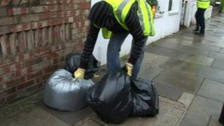 Dustbin man collecting bin bags