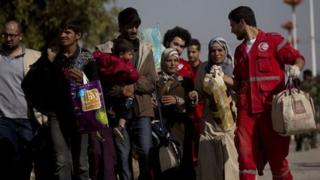 People walk from the rebel-held suburb of Muadhamiya to government-held territory, helped by aid workers