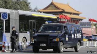 A policeman stands guard next to a special police vehicle near Tiananmen Gate, in Beijing, 29 October 2013