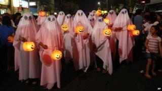People dressed in ghost costumes