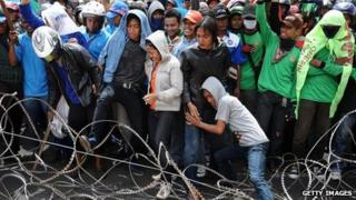 Protesters attempt to dismantle barbed wire barricades during a protest demanding higher wages on 31 October 2013 in Surabaya