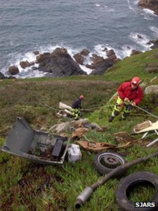 Cliff rescue team members retrieving rubbish