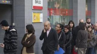People queue outside a government unemployment office in Madrid, Spain