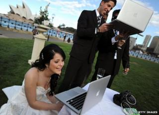 Bride and groom use laptops
