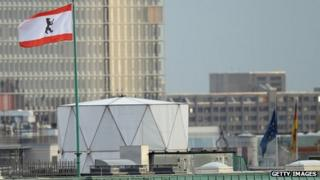 The Berlin flag flies next to a white structure that, according to media reports, contains sophisticated electronic surveillance equipment and stands on top of the British embassy