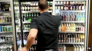 Man at fridge containing alcohol