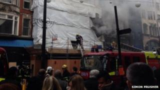 Pedestrians cover their faces as they pass the fire in Oxford Street