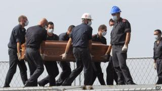 Rescuers carrying coffin of a Lampedusa migrant, 12 Oct 13