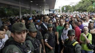 National Guard Soldiers stand on guard as shoppers wait outside an electronics store in Caracas on 9 November, 2013