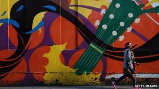 Woman walks past street art in Dublin