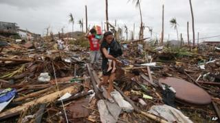 A woman carries her baby across an area damaged by Typhoon Haiyan at Tacloban city, Leyte province, central Philippines on 12 November 2013