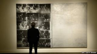 A man looks at Andy Warhol's Silver Car Crash painting