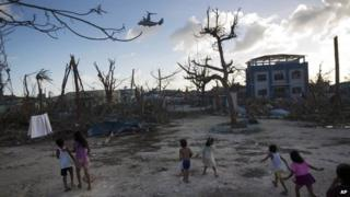 Children run towards a US military aircraft as it arrives to distribute aid in Guiuan, Philippines on 14 November 2013