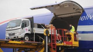 Ground staff load equipment onto a Boeing 747 at East Midlands Airport headed for Cebu in the Philippines