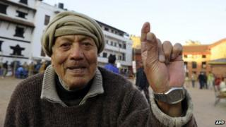 A Nepalese man shows his finger after an election official marked it with indelible ink at a polling station in Kathmandu on 19 November 2013
