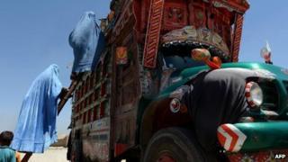 Afghan refugees board a truck in Kabul, June 2013
