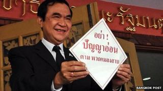Thai Interior Minister Jarupong Ruangsuwan holds up a protest sign