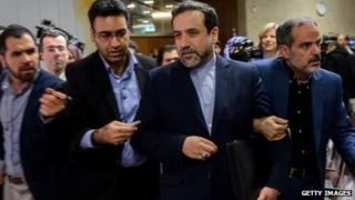 Iran's Deputy Foreign Minister Abbas Araqchi is surrounded by journalists during nuclear talks in Geneva on November 10, 2013.