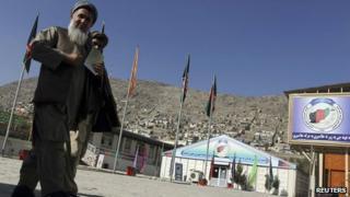 Afghan men walk near a registration area for the Loya Jirga, in Kabul