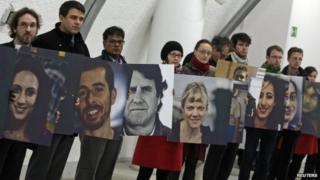 Greenpeace activists hold pictures showing the 30 people arrested in Russia over a protest against Arctic oil drilling on November 13, 2013