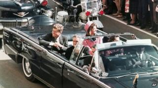 President John F. Kennedy's motorcade travels through Dallas, Texas on 22 November 1963