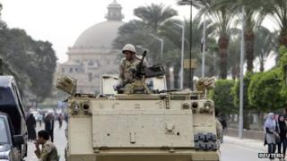 A soldier in an armoured personnel carrier at the main gate of Cairo University