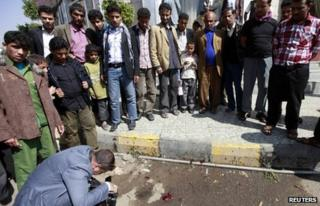 A man takes a photograph of the scene of the shooting in Sanaa (26 November 2013)