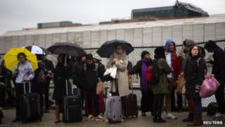 Travellers wait to board a bus in New York on 27 November 2013