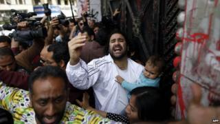 Egyptian pro-democracy activist and opponent of Egypt's ruling Muslim Brotherhood, Alaa Abd Fattah, arrives at the general prosecutor office in Cairo holding his son on March 26, 2013, to turn himself in for questioning, a day after an order for his arrest