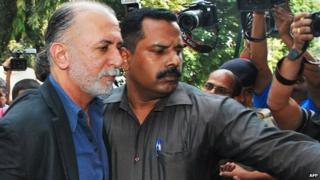 Indian magazine editor, Tarun Tejpal, is escorted by police officials from a courthouse after being remanded in police custody in Panaji on December 1, 2013