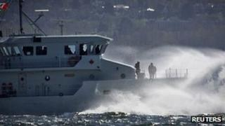 Waves crash over the bow of the Royal Canadian Navy's HMCS Caribou patrol ship as it leaves Burrard Inlet on a windy day in West Vancouver, British Columbia 10 April 2013