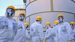 A team of International Atomic Energy Agency (IAEA) experts check out water storage tanks at Fukushima