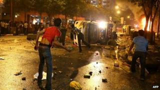 Young men hurt large stones from behind an overturned police van in Little India, Singapore