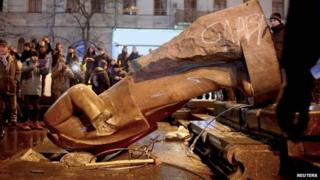 People surround a statue of Soviet state founder Vladimir Lenin, which was toppled by protesters during a rally organized by supporters of EU integration in Kiev, December 8, 2013