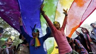 Participants dance under a a rainbow flag as they attend the sixth Delhi Queer Pride parade, an event promoting gay, lesbian, bisexual and transgender rights, in Delhi.