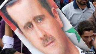 Supporters hold a poster of Syrian President Bashar Assad during a rally on October 12, 2011.