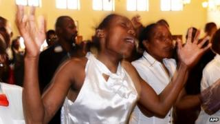 "Member of a local choir sing and dance during a memorial service for Nelson Mandela at the Komkhulu or ""Great Place"" in Mvezo."