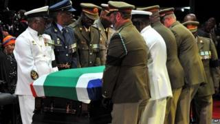 Former South African President Nelson Mandela's casket is taken out of the makeshift tent by military pall bearers following his funeral service in Qunu