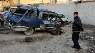 An Iraqi man inspects a minibus damaged in a car bomb attack in Baghdad